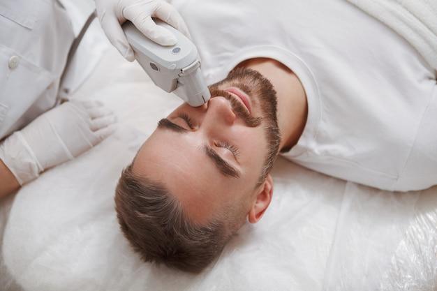 Nahaufnahme eines bärtigen mannes, der laser-gesichtsbehandlung durch professionelle kosmetikerin genießt