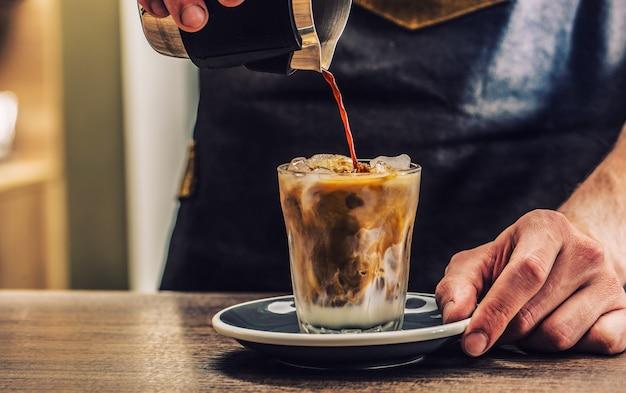 Nahaufnahme eines barista, der fres eiskaffee auf der bartheke macht.