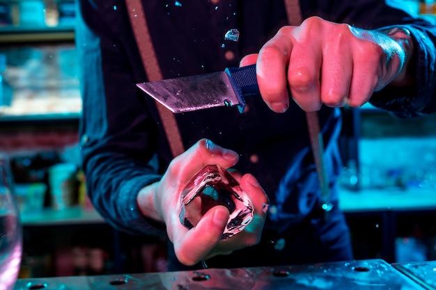 Nahaufnahme eines barmanns, der ein großes stück eis auf der bartheke mit einer speziellen barausrüstung für einen cocktail zerdrückt?