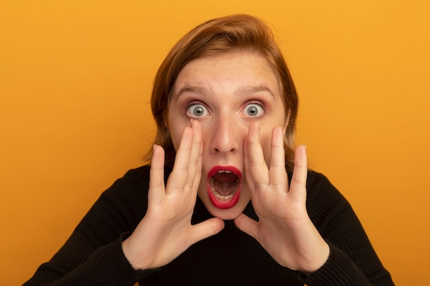Nahaufnahme eines beeindruckten jungen blonden mädchens, das die hände in der nähe des mundes hält und flüstert, isoliert auf oranger wand