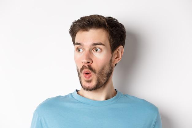 Nahaufnahme eines beeindruckten kaukasischen mannes, der wow sagt, verblüfft nach links schaut, promotion-deal auscheckt, weißer hintergrund. platz kopieren