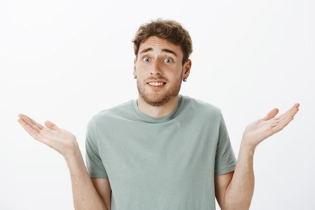 Nahaufnahme eines befragten ungeschickten gutaussehenden mannes in ohrringen, der ahnungslos mit den schultern zuckt und die handflächen spreizt, ahnungslos ist und nichts weiß, was zu tun ist