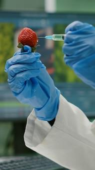 Nahaufnahme eines biologen, der erdbeeren mit dna-flüssigkeit injiziert, die früchte für pharmazeutische medizinische experimente überprüft