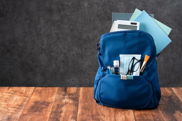 Nahaufnahme eines blauen rucksacks mit schulmaterial über holztisch und schwarzem hintergrund, zurück zum schulkonzept.
