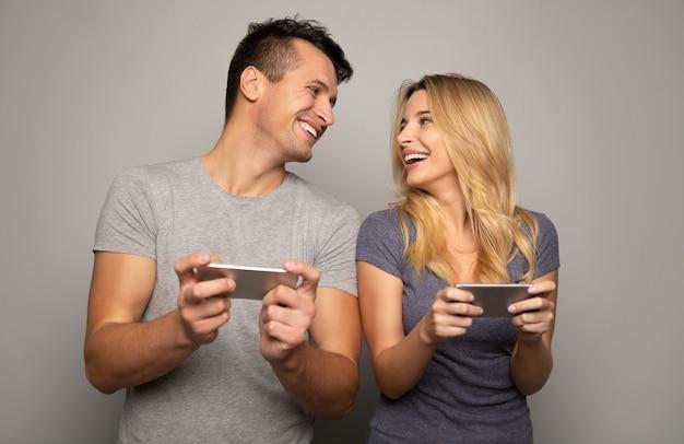 Nahaufnahme eines blonden mädchens und ihres hübschen freundes, die mit konzentrierten gesichtsausdrücken handyspiele auf ihren smartphones spielen.