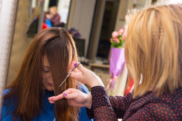 Nahaufnahme eines blonden stylisten, der haare eines jungen brünetten kunden schneidet - friseur, der im salon abgewinkelte pony in das haar eines jungen weiblichen kunden schneidet