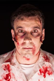 Nahaufnahme eines blutigen zombies auf schwarzem hintergrund für halloween. kreatives make-up.