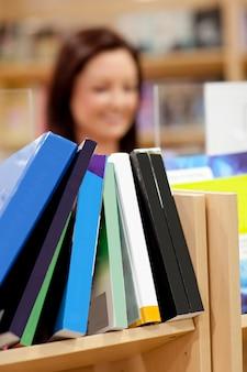 Nahaufnahme eines bücherregals in einer bibliothek mit weiblichem kunden im hintergrund