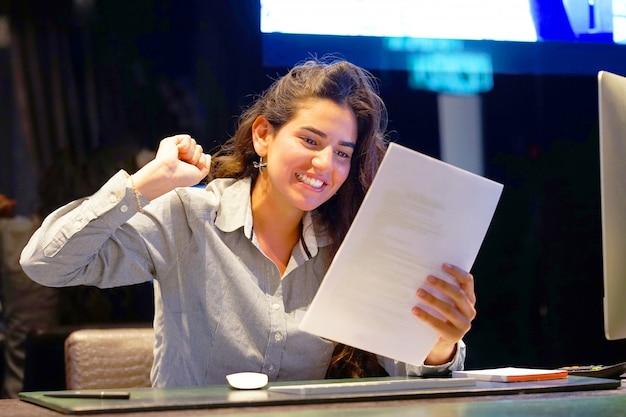 Nahaufnahme eines büroangestellten. glückliche dame, die die guten nachrichten schriftlich genießt. ein euphorisches mädchen ist glücklich, nachdem es in einem schriftlichen brief gute nachrichten gelesen, einen kredit genehmigt und seinen job erhöht hat.