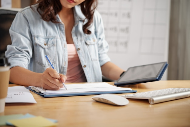 Nahaufnahme eines büroangestellten in freizeitkleidung, der am tisch sitzt und daten auf dem tablet analysiert, während er einen bericht im büro erstellt