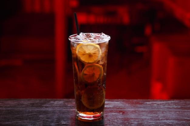 Nahaufnahme eines cuba libre-cocktails im langen glas, gin, stehend auf der bartheke, lokalisiert auf einem rotlichtraum.