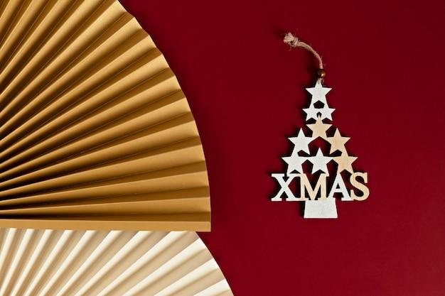 Nahaufnahme eines dekorativen weihnachtsbaumes aus goldenen sternen mit einem papierfächer. stilvolle moderne weihnachtsdekorationen auf purpurroter wand