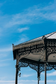 Nahaufnahme eines details des schmiedeeisernen pavillons vor blauem himmel in alcalá de henares, spanien