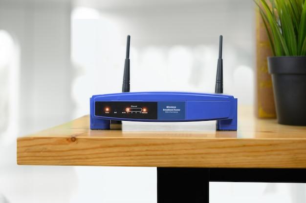 Nahaufnahme eines drahtlosen routers und des mannes, der zu hause smartphone auf büro des wohnzimmers verwendet
