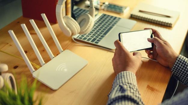 Nahaufnahme eines drahtlosen routers und des mannes, der zu hause smartphone auf ofiice wohnzimmer verwendet