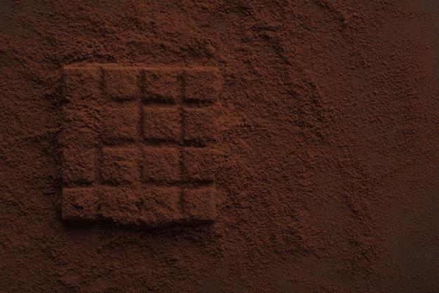 Nahaufnahme eines dunklen schokoriegels, der mit schokoladenpulver bedeckt ist