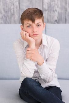 Nahaufnahme eines durchdachten jungen, der auf dem sofa betrachtet kamera sitzt