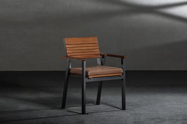 Nahaufnahme eines einfachen modernen stuhls mit metallischen beinen in einem raum mit grauen wänden