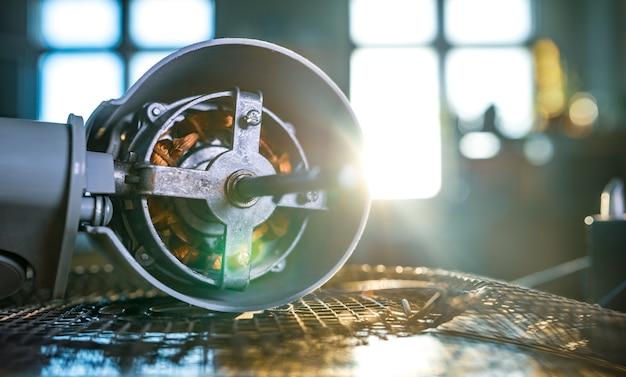 Nahaufnahme eines eisenmotors vom heimlüfter liegt auf einem tisch während der vorbeugenden reinigung, schmierung und reparatur in einer fachwerkstatt. das konzept der reparatur und wiederherstellung beschädigter geräte