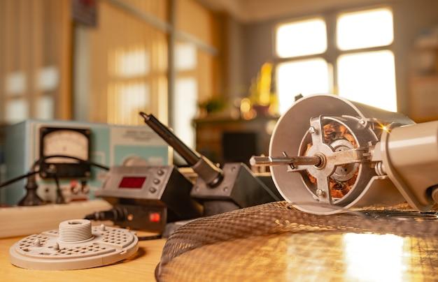 Nahaufnahme eines eisenmotors von heimlüfter und testwerkzeugen liegt auf einem tisch in der werkstatt. das konzept der reparatur und wiederherstellung beschädigter geräte