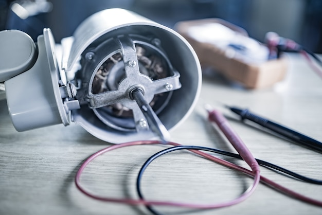 Nahaufnahme eines eisenmotors von zu hause aus lüfter und testwerkzeugen liegt während der reparatur in einer fachwerkstatt auf einem tisch. das konzept der reparatur und wiederherstellung beschädigter geräte