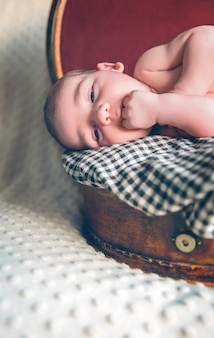 Nahaufnahme eines entzückenden neugeborenen, das über einer karierten decke auf einem vintage-reisekoffer liegt?