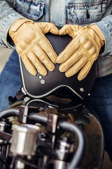Nahaufnahme eines erfahrenen fahrers. nahaufnahme motorrad detail. schwarzer helm und gelbe handschuhe eines motorradfahrers.
