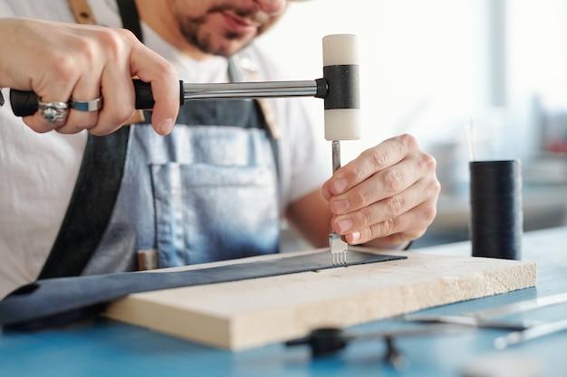 Nahaufnahme eines erfahrenen handwerkers, der mit einem hammer auf den stichmeißel schlägt, während er nählöcher in leder macht