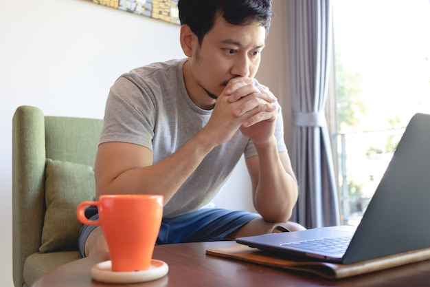 Nahaufnahme eines ernsten asiatischen mannes, der an seinem laptop im kaffeecafé arbeitet.
