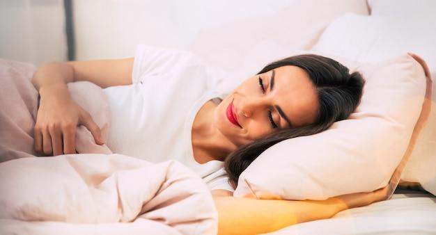 Nahaufnahme eines extrem schönen mädchens, das lächelt, während es fest in ihrem bett mit der rosafarbenen bettwäsche schläft.
