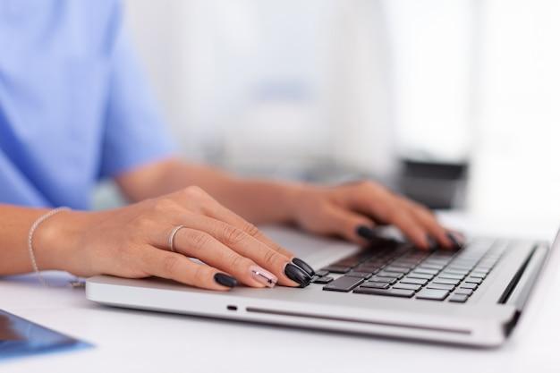 Nahaufnahme eines facharztes, der auf laptop im krankenhausbüro arzt tippt, der in ...
