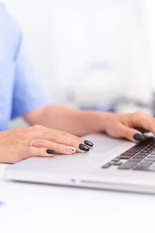 Nahaufnahme eines facharztes, der im krankenhausbüro auf laptop schreibt. arzt sucht in krankenhausdatenbank mit laptop im krankenhausschrank, tastatur, job.