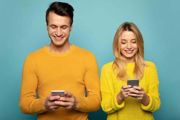 Nahaufnahme eines familienpaares in gelben pullovern, die vorne stehen und mit ihren smartphones im internet surfen.