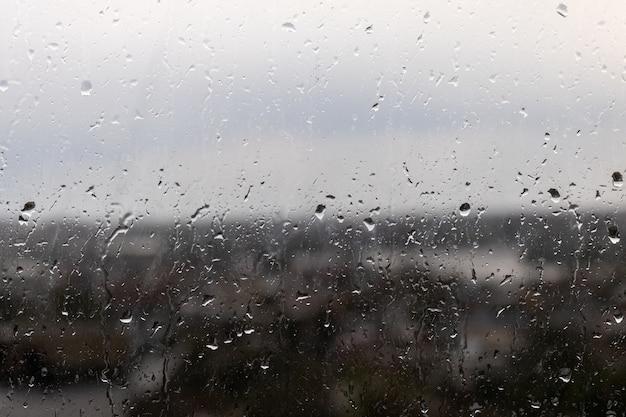 Nahaufnahme eines fensters an einem regnerischen düsteren tag, regentropfen, die das fenster hinunter rollen