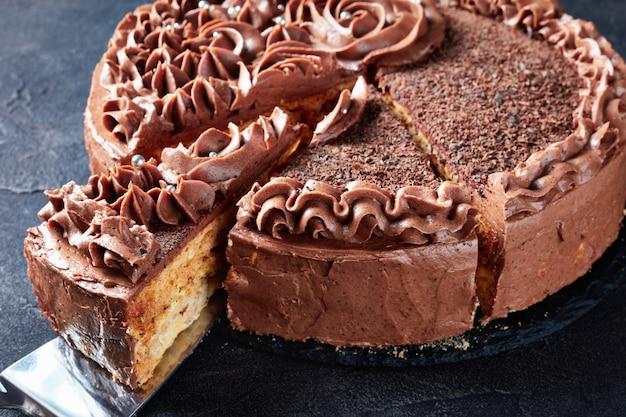 Nahaufnahme eines festlichen schokoladenbaiser-kuchens mit schokoladenbuttercreme-rosen und silbernem essbarem dragee, geschnitten in scheiben auf einem teller auf einem betontisch, horizontale ansicht von oben