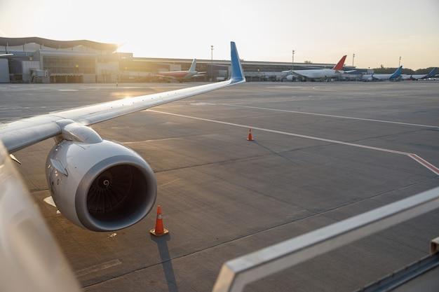 Nahaufnahme eines flügels eines verkehrsflugzeugs in der nähe des terminals in einem flughafen bei sonnenuntergang. flugzeug, reisekonzept
