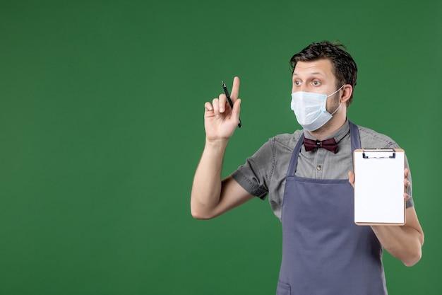 Nahaufnahme eines fokussierten männlichen kellners in uniform mit medizinischer maske und mit einem bestellbuchstift, der auf grünem hintergrund nach oben zeigt