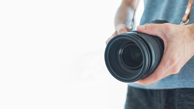 Nahaufnahme eines fotografen, der dslr kamera auf weißem hintergrund hält