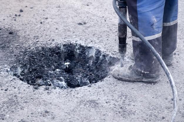 Nahaufnahme eines fotos der berufsarbeiter in der uniform, die asphaltstraße repariert