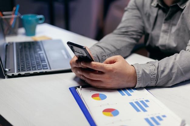 Nahaufnahme eines freiberuflers, der überstunden auf dem smartphone-sitzarbeitsplatz schreibt. geschäftsmann, der seine zelle verwendet, um eine sms zu senden, während er spät nachts im büro arbeitet, um eine frist zu beenden.