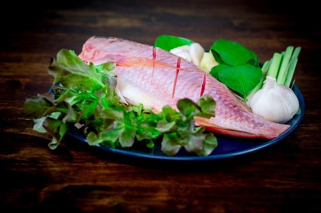 Nahaufnahme eines frischen fischs und gemüses in keramikgeschirr zum kochen vorbereitet