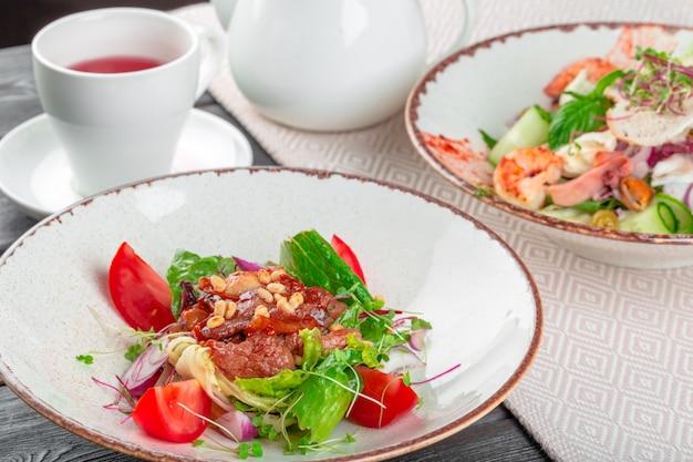 Nahaufnahme eines frischen grünen salats mit geschnittenem gebratenem lendensteak