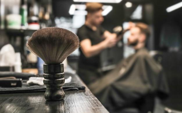 Nahaufnahme eines friseur-toolkits aus holzbürste, trimmer und schere, das auf einer barbershop-theke liegt.