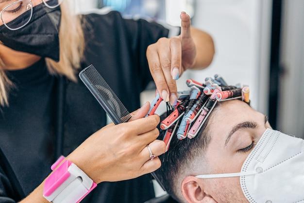 Nahaufnahme eines friseurs, der das haar eines mannes mit rollen kräuselt, während er eine maske verwendet