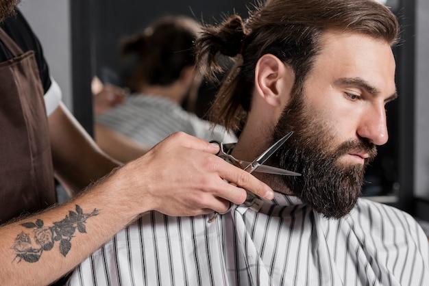 Nahaufnahme eines friseurs, der den bart des männlichen kunden schneidet