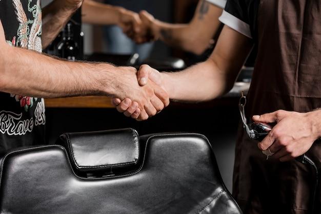 Nahaufnahme eines friseurs, der hände mit männlichem kunden rüttelt
