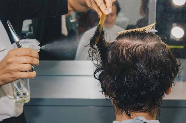 Nahaufnahme eines friseurs schneidet das nasse braune haar eines kunden in einem salon. friseur schneidet eine frau. seitenansicht einer hand, die haar mit einer schere schneidet.