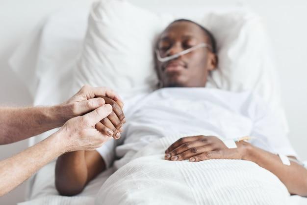 Nahaufnahme eines fürsorglichen verwandten, der die hand eines afroamerikanischen mannes hält, der im krankenhausbett liegt, kopierraum
