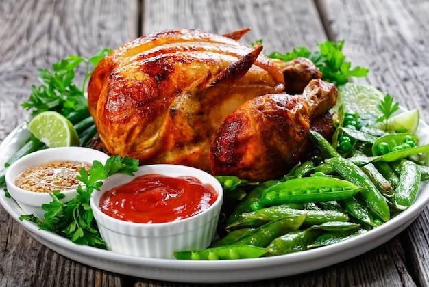 Nahaufnahme eines gegrillten huhns serviert mit gebratenen schoten von grünen erbsen, frischen frühlingszwiebeln, petersilie, limette, tomatensauce und vollkornsenf auf einem weißen teller auf einem rustikalen holztisch, landschaftsansicht