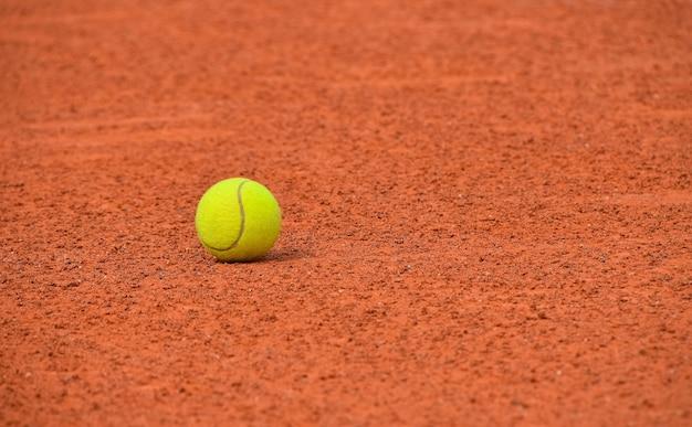 Nahaufnahme eines gelben filztennisballs auf rotbraunem sandplatz, niedriger betrachtungswinkel